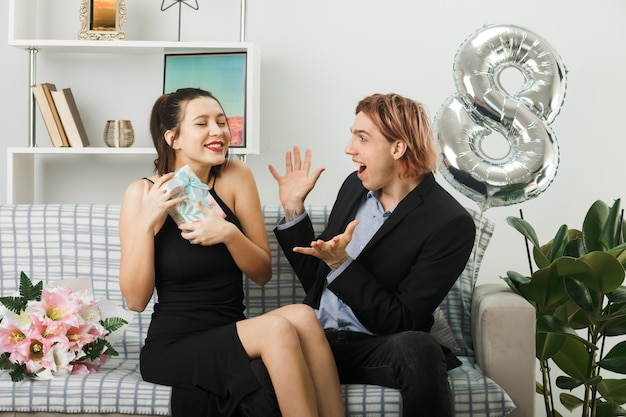 Pleased young couple on happy women day girl holding present guy spreading hands sitting on sofa in living room