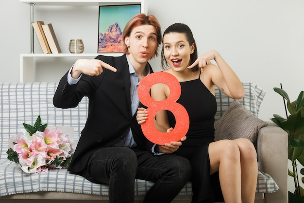 Pleased young couple on happy women day holding and points at number eight sitting on sofa in living room