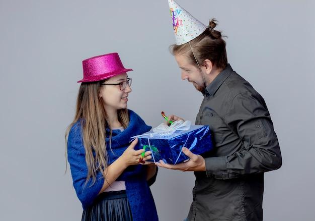 La giovane coppia lieta si guarda l'un l'altro tenendo la ragazza di scatola regalo con gli occhiali che indossa il cappello rosa tiene il fischietto e bell'uomo in berretto di compleanno che tiene il fischio isolato sul muro bianco
