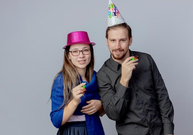 La giovane coppia felice guarda la ragazza con gli occhiali che indossa il cappello rosa tiene il fischio e l'uomo bello nel berretto di compleanno che tiene il fischio isolato sul muro bianco