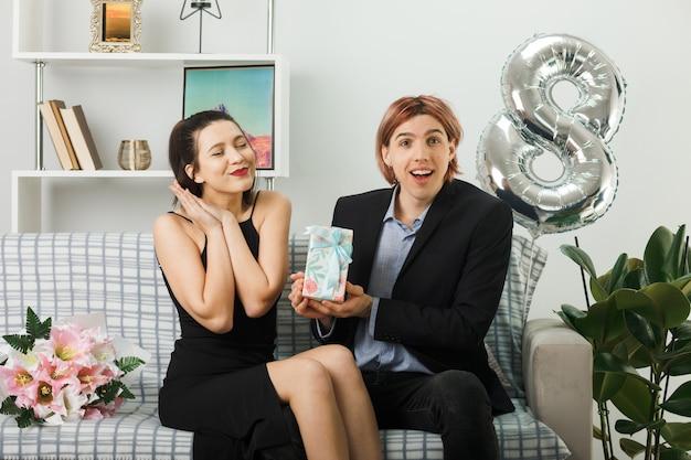 幸せな女性の日の男の幸せな若いカップルは、リビングルームのソファに座っている幸せな女の子にプレゼントを贈る