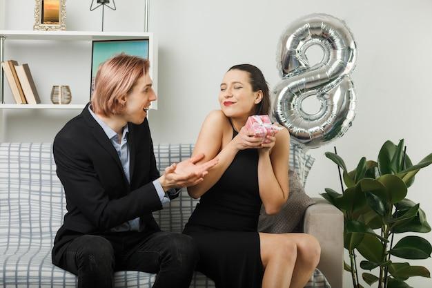 Довольная молодая пара в счастливый женский день держит подарок, сидя на диване в гостиной