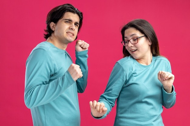 Pleased young couple on valentines day dancing isolated on pink background