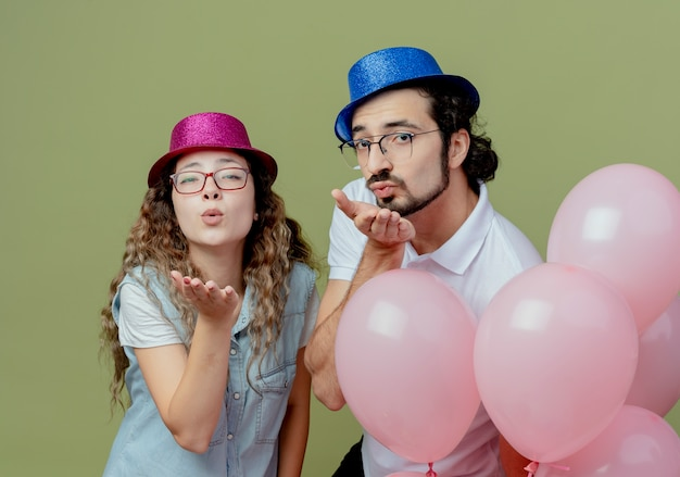 Pleased young couple wearing pink and blue hat standing behind balloons and showing kiss gesture