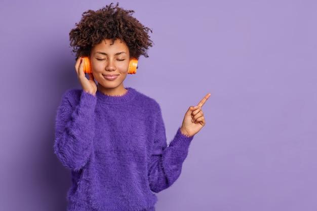 Довольная молодая кудрявая афроамериканка с закрытыми глазами, с вьющимися волосами наслаждается любимой мелодией, одетая в повседневную одежду, указывает на пространство для копирования