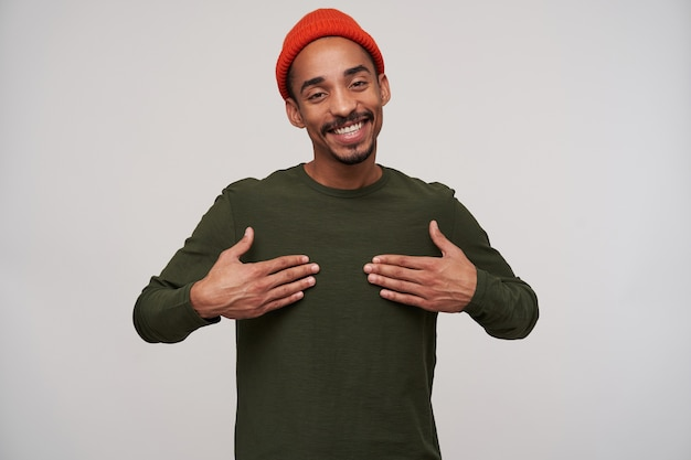 Довольный молодой темноволосый бородатый темнокожий парень, держащий ладони на груди и счастливо улыбающийся, находясь в хорошем настроении, стоя на белом