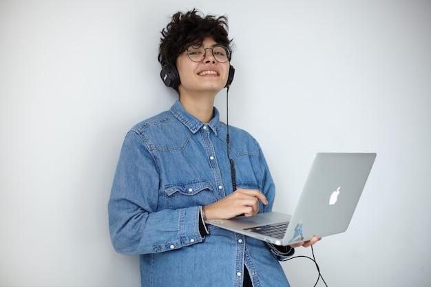Lieta giovane signora bruna riccia dai capelli scuri in camicia di jeans blu ascoltando file audio con auricolari e sorridendo leggermente alla fotocamera, tenendo il laptop in mano mentre si trova su sfondo bianco