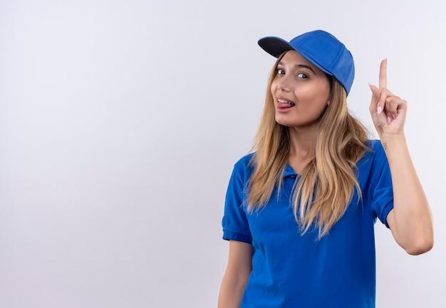 파란색 유니폼과 혀와 포인트를 보여주는 모자를 입고 기쁘게 젊은 배달 소녀 복사 공간이 흰 벽에 고립