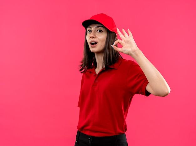 Lieta giovane ragazza delle consegne che indossa la maglietta polo rossa e cappello sorridente che mostra segno giusto in piedi sopra il muro rosa