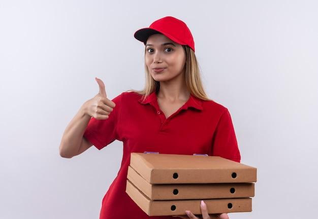 빨간 유니폼과 모자를 들고 기쁘게 젊은 배달 소녀 피자 상자 그녀의 엄지 손가락을 흰색 벽에 격리