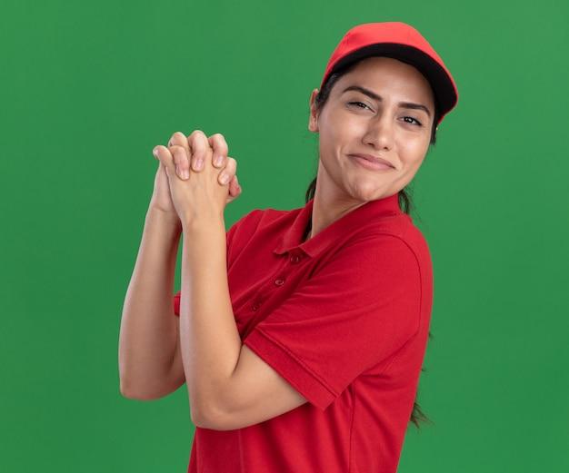 녹색 벽에 고립 된 핸드 셰이커 제스처를 보여주는 유니폼과 모자를 입고 기쁘게 젊은 배달 소녀