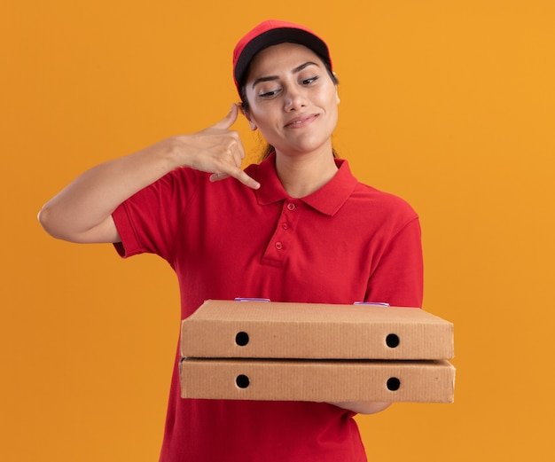 Lieta giovane ragazza delle consegne che indossa l'uniforme e il cappuccio che tiene le scatole per pizza che mostrano il gesto della telefonata isolato sulla parete arancione