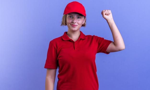 Compiaciuta giovane ragazza delle consegne che indossa l'uniforme e il berretto che mostra il gesto di sì isolato sulla parete blu