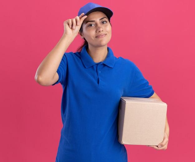 분홍색 벽에 고립 된 상자와 모자를 들고 모자와 유니폼을 입고 기쁘게 젊은 배달 소녀