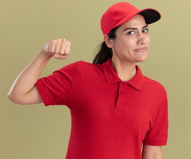 올리브 녹색 벽에 고립 된 강한 제스처를 보여주는 모자와 유니폼을 입고 기쁘게 젊은 배달 소녀