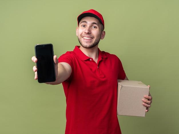 Felice giovane fattorino che indossa l'uniforme, tiene in mano una scatola di cartone e mostra lo smartphone
