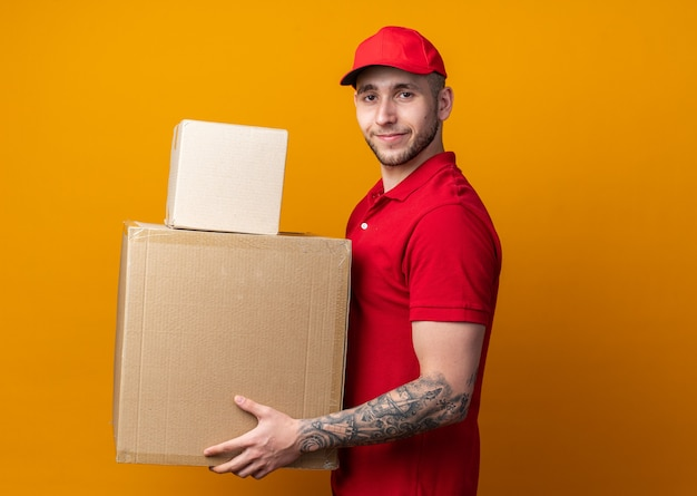 상자를 들고 모자와 유니폼을 입고 기쁘게 젊은 배달 남자