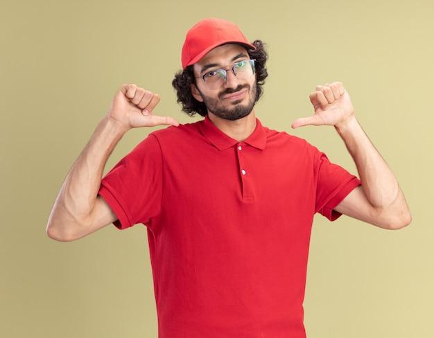 빨간색 유니폼을 입고 안경을 쓴 모자를 쓴 행복한 젊은 배달원은 올리브 녹색 벽에 고립된 자신을 가리키는 정면을 바라보고 있다