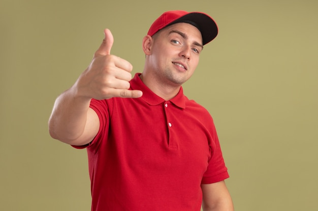 Felice giovane fattorino che indossa l'uniforme e il berretto che mostra il gesto di una telefonata isolato su una parete verde oliva