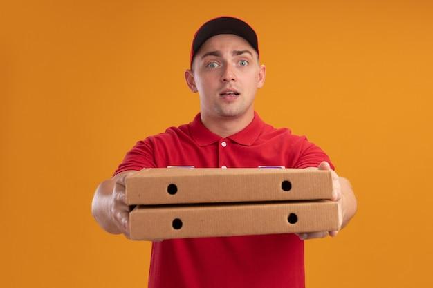 Довольный молодой доставщик в униформе с кепкой, протягивающей коробки для пиццы спереди, изолированные на оранжевой стене