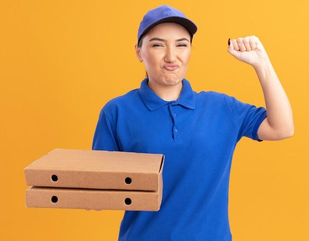 파란색 유니폼과 모자는 오렌지 벽 위에 서있는 승자처럼 유쾌하게 주먹을 높이 웃는 정면을보고 피자 상자를 들고 기쁘게 젊은 배달 여자