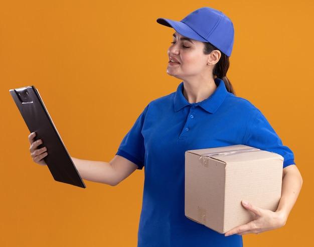 クリップボードを見て、カードボックスとクリップボードを保持している制服とキャップで若い配達の女性を喜ばせる