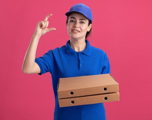 Довольная молодая женщина-доставщик в униформе и кепке, держащая упаковки с пиццей, делает небольшой жест, изолированный на розовой стене