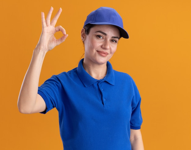 Pleased young delivery woman in uniform and cap doing ok sign