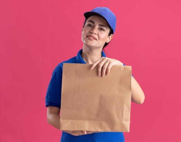 Felice giovane donna delle consegne in uniforme e berretto che tiene il pacchetto di carta isolato sulla parete rosa con spazio per le copie