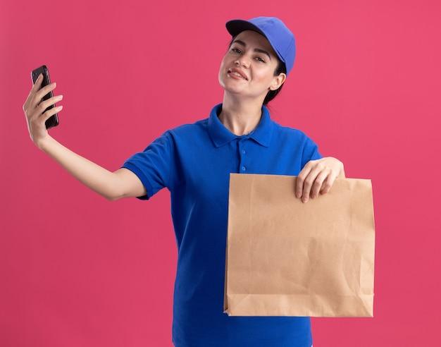 Felice giovane donna delle consegne in uniforme e berretto con in mano un pacchetto di carta e un telefono cellulare