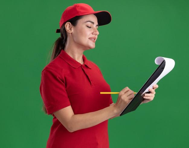Felice giovane donna delle consegne in uniforme e berretto