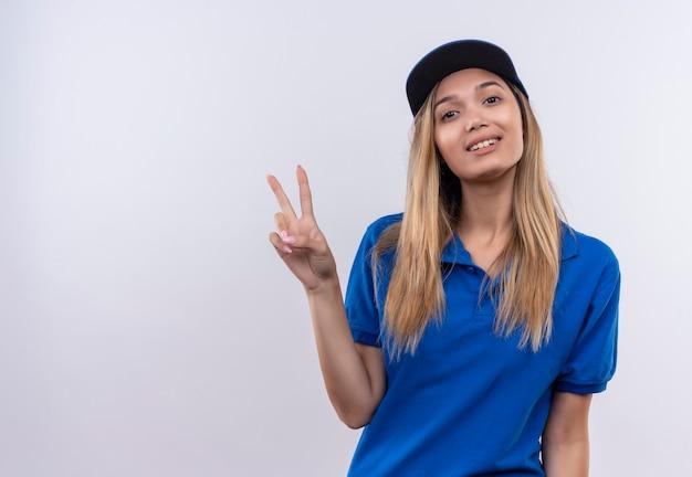 青い制服と平和のジェスチャーを示すキャップを身に着けている若い配達の女性を喜ばせる