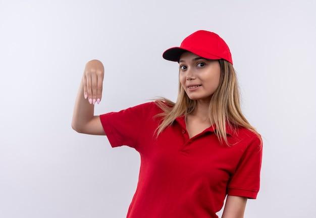 Felice giovane donna di consegna che indossa l'uniforme rossa e berretto che finge di tenere qualcosa