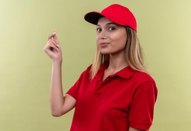 Felice giovane donna delle consegne che indossa l'uniforme rossa e cappuccio che mostra il gesto di punta