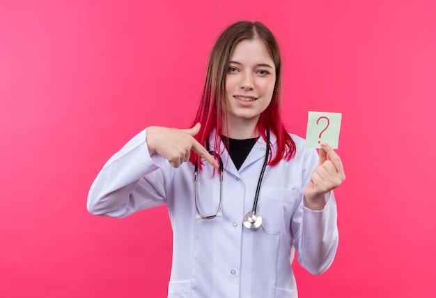 聴診器の医療用ガウンを着て喜んでいる若い医者の女の子は、ピンクの孤立した背景に彼女の手で紙の疑問符を指しています