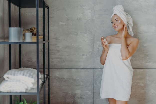 Pleased young european woman applies face lotion holds bottle of cosmetic product wrapped in white bath towel stands against grey wall in bathroom. people cosmetology beauty and cleansing concept