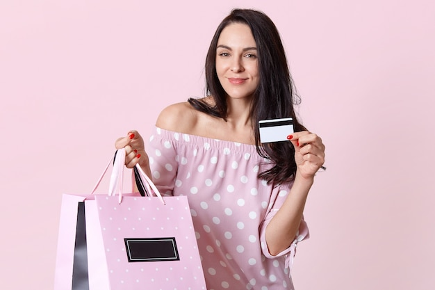 Pleased young european woman enjoys shopping on weekend, holds plastic card, shopping bags, spends money on clothes, dressed in polka dot dress, models on pink. shopaholic