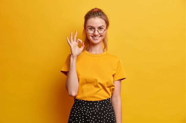 Довольная молодая европейка делает нормальный жест, показывает отличную работу, говорит, что все хорошо, довольна, дает положительный отзыв, думает, что ваша идея идеальна, носит круглые очки, повседневная одежда