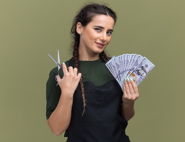 オリーブグリーンの壁に分離されたはさみで現金を保持している制服を着た若い女性の理髪師を喜ばせる