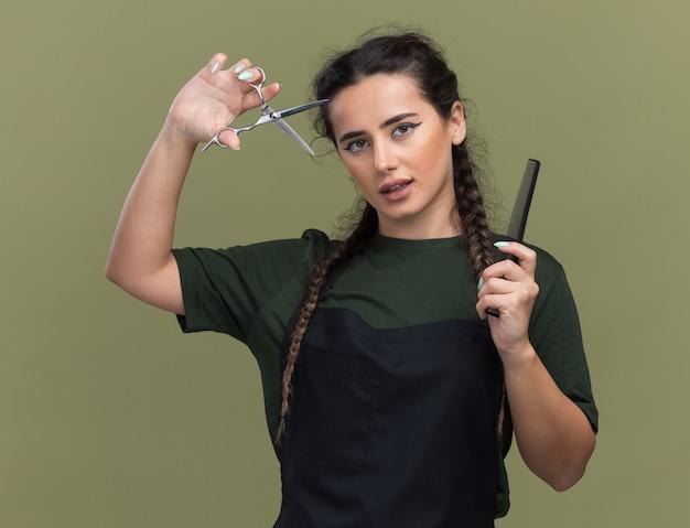 オリーブグリーンの壁に分離された櫛を保持し、はさみを上げる制服を着た若い女性の理髪師を喜ばせる