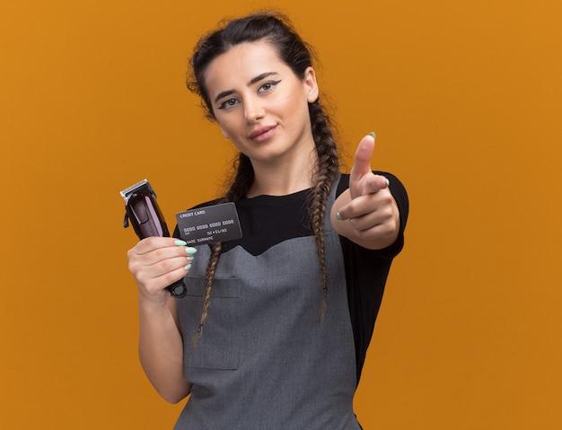 Lieta giovane donna barbiere in uniforme che tiene la carta di credito e punti tagliacapelli isolati sulla parete arancione