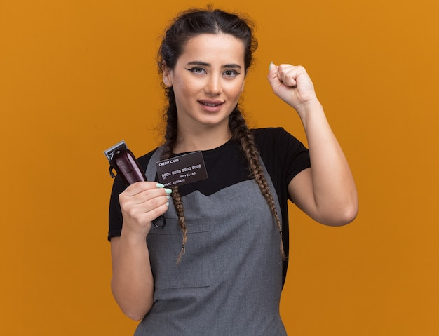 Pleased young female barber in uniform holding credit card and hair clippers showing yes gesture isolated on orange wall