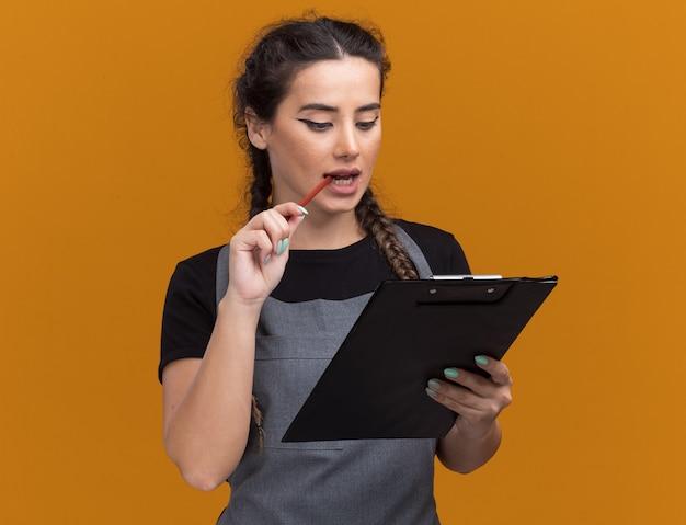 Lieto giovane barbiere femminile in uniforme che tiene e che esamina appunti mettendo la matita sulla bocca isolata sulla parete arancione