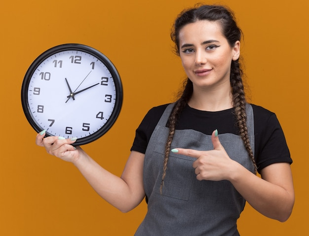 Pleased young female barber in uniform holding and points at wall clock isolated on orange wall
