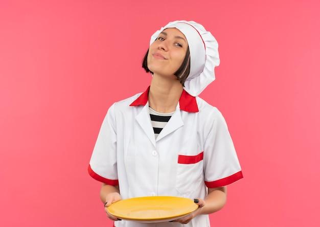 Lieta giovane cuoca in uniforme da chef tenendo piatto vuoto isolato sulla parete rosa