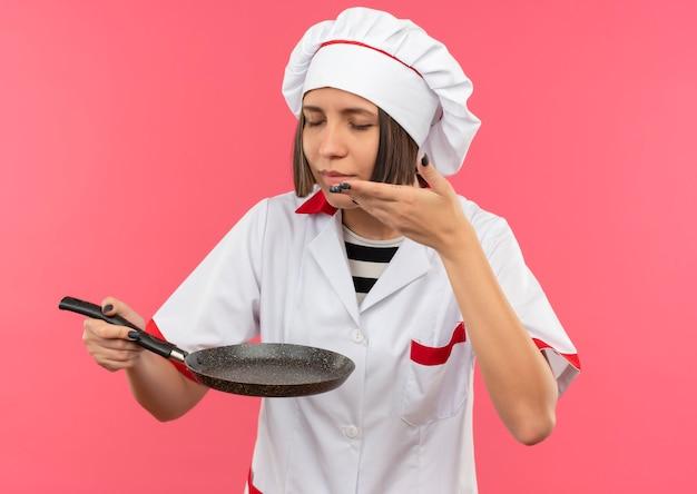 Lieta giovane cuoca in uniforme da chef tenendo la padella e annusando con gli occhi chiusi e tenendo la mano sull'aria isolata sul muro rosa