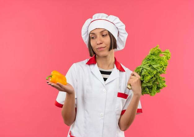 Lieta giovane cuoca in uniforme da chef tenendo pepe e lattuga e guardando pepe isolato sulla parete rosa
