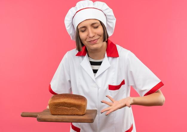 Lieta giovane cuoca in uniforme da chef tenendo e indicando con la mano al tagliere con pane su di esso con gli occhi chiusi isolati su sfondo rosa