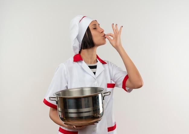 Lieta giovane cuoca in uniforme da chef tenendo la pentola e facendo gustoso gesto con gli occhi chiusi isolati sul muro bianco