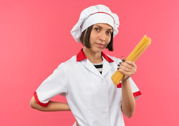 Lieta giovane cuoca in uniforme da chef tenendo gli spaghetti e tenendo la mano dietro la schiena isolata sulla parete rosa